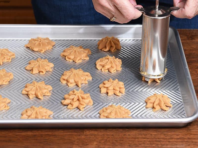 Baker Using Cookie Press